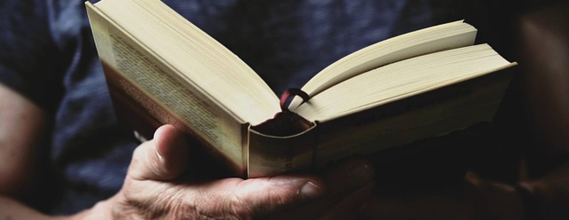 aufgeschlagender Roman in der Hand